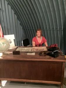 Kim seated at JFK's Bomb Shelter Desk